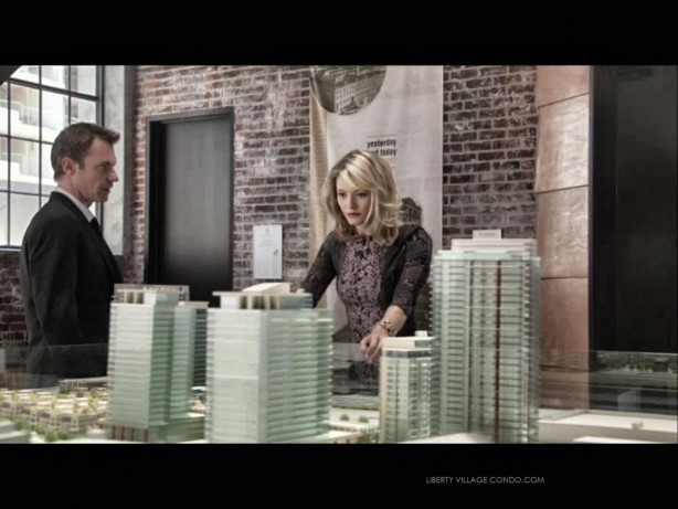 Chris Vance and Sarah Allen in S1 Ep 7 of Transporter in the CanAlfa sales office looking at a scale model of Liberty Village